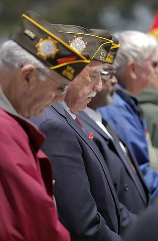 Veterans bow their heads during closing prayers for Memorial Day services at the San Francisco National Cemetery on Monday. Photo: Carlos Avila Gonzalez, The Chronicle