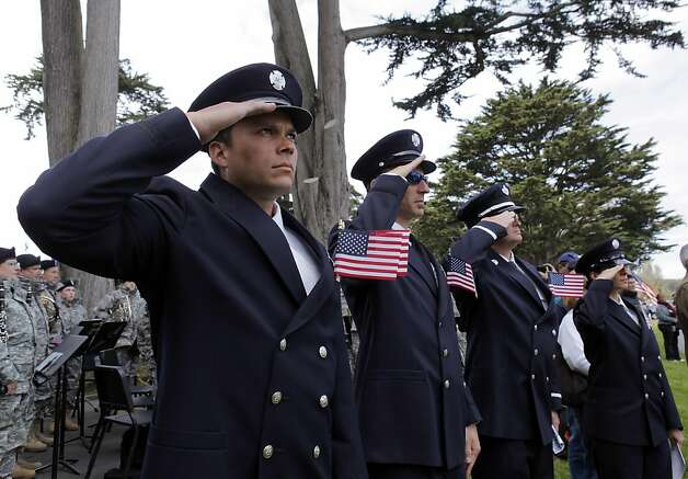 Members of the San Francisco Fire Department salute the raising of the flag at the end of ceremonies for Memorial Day at San Francisco National Cemetery on Monday. Photo: Carlos Avila Gonzalez, The Chronicle