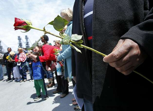 People were given flowers to throw off the old USS Hornet aircraft carrier as Memorial Day was celebrated on board Monday in Alameda. Photo: Brant Ward, The Chronicle