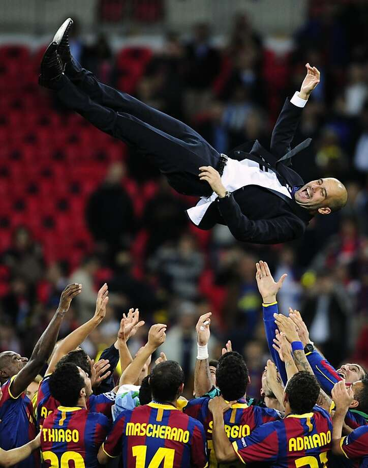 The Barcelona team throw coach Pep Guardiola in the air after winning the Champions League final soccer match against Manchester United at Wembley Stadium, London, Saturday, May 28, 2011. Photo: Matt Dunham, AP