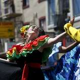On Mission Street, a man and woman in colorful costume dance to a pounding drum beat at the annual Carnaval parade and celebration in San Francisco's Mission District on Sunday.