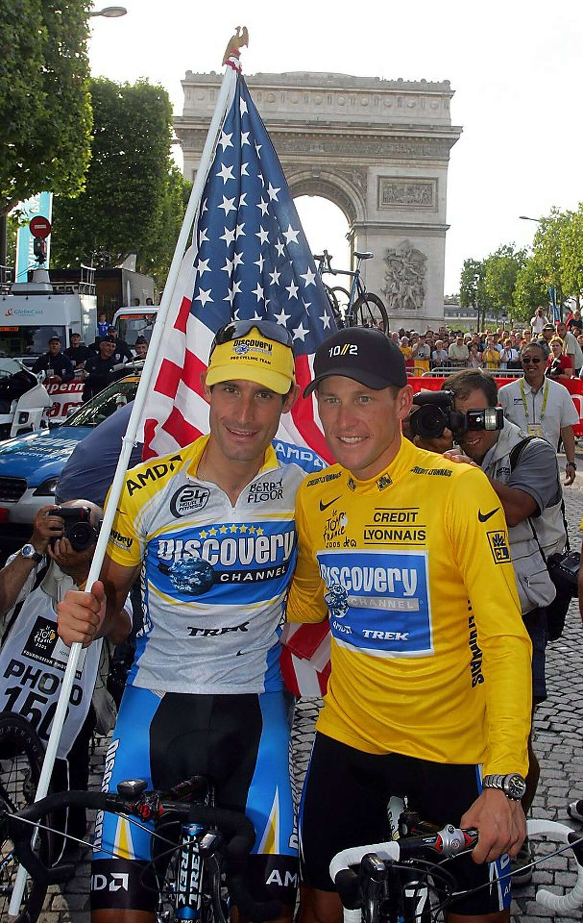 """FILE - In this July 24, 2005 file photo, Lance Armstrong, right, and his Discovery team colleague George Hincapie pose for photographers on the Champs Elysees during a victory parade after Armstrong won his 7th straight Tour de France cycling race in Paris. A report by """"60 Minutes"""" says Hincapie, a longtime member of Lance Armstrong's inner circle, has told federal authorities he saw the seven-time Tour de France winner use performance-enhancing drugs. A segment of the report aired Friday night, May 20,2011 on the """"CBS Evening News."""""""
