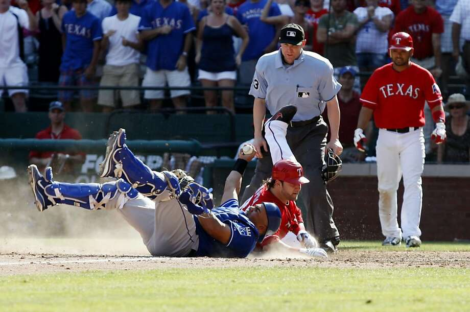 Kansas City Royals catcher Brayan Pena and Texas Rangers Mike Napoli (25) collide at home plate in the bottom of the ninth inning as Napoli scored on a single to give the Rangers a  7-6  over the Royals Sunday May 29, 2011 at Rangers Ballpark in Arlington, Texas, Photo: Sharon Ellman, AP