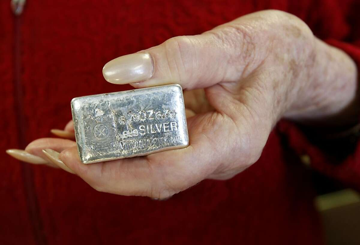 A sales woman at the Marshall Mint store in Virginia City displays a bar of silver taken from a mine near Virginia City. Comstock Mining Inc. is planning to pit-mine claims near Virginia City, Nevada much to the dismay of local residents, who live with the environmental disasters of past mining companies.