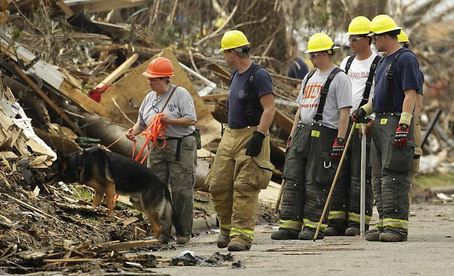 Kim Stuart, from Little River, Ark., and her dog Thunder along with other searchers look for bodies in a devastated Joplin, Mo. neighborhood Saturday, May 28, 2011. An EF-5 tornado tore through much of the city Sunday, damaging a hospital and hundreds ofhomes and businesses and killing at least 139 people. Photo: Charlie Riedel, AP