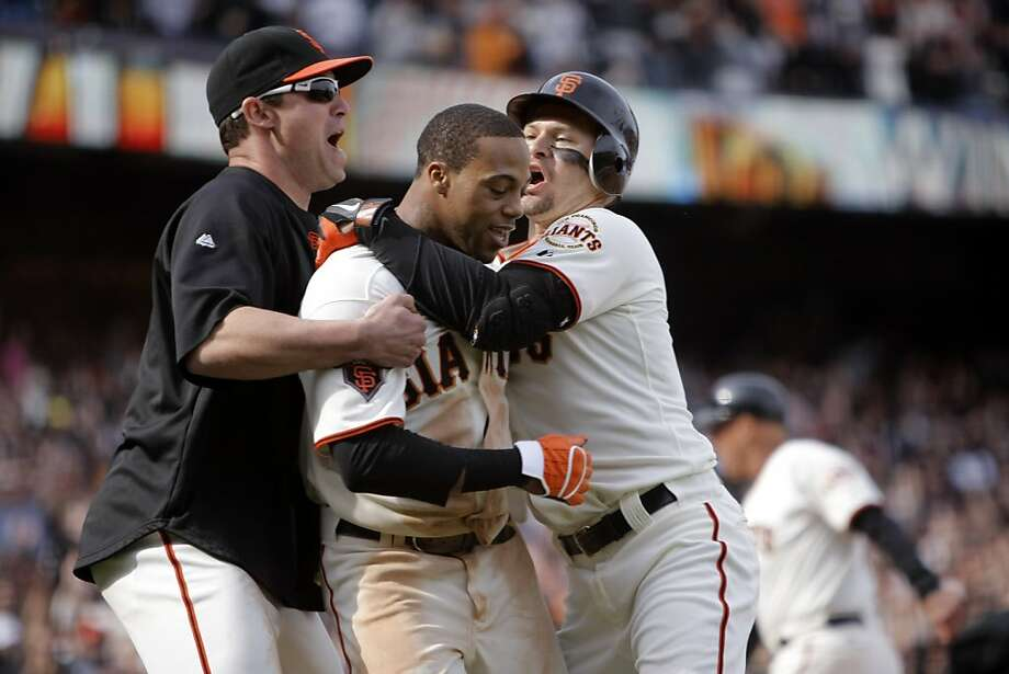 San Francisco Giants' Darren Ford is congratulated by Pat Burrell and Cody Ross after scoring the winning run off of Giants' Emmanuel Burriss' RBI hit in the 11th inning. As the San Francisco Giants take on the Oakland Athletics at AT&T Park in San Francisco, Calif., on Sunday, May 22, 2011. Photo: Thomas Levinson, The Chronicle