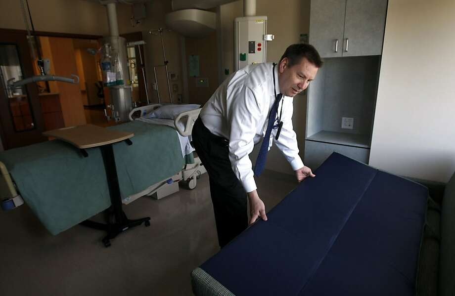 Registered nurse Jim Benney opens a foldout bed, which is provided in all rooms for patient's family members, at the new Mills-Peninsula Hospital in Burlingame, Calif. on Friday, May 6, 2011. Photo: Paul Chinn, The Chronicle