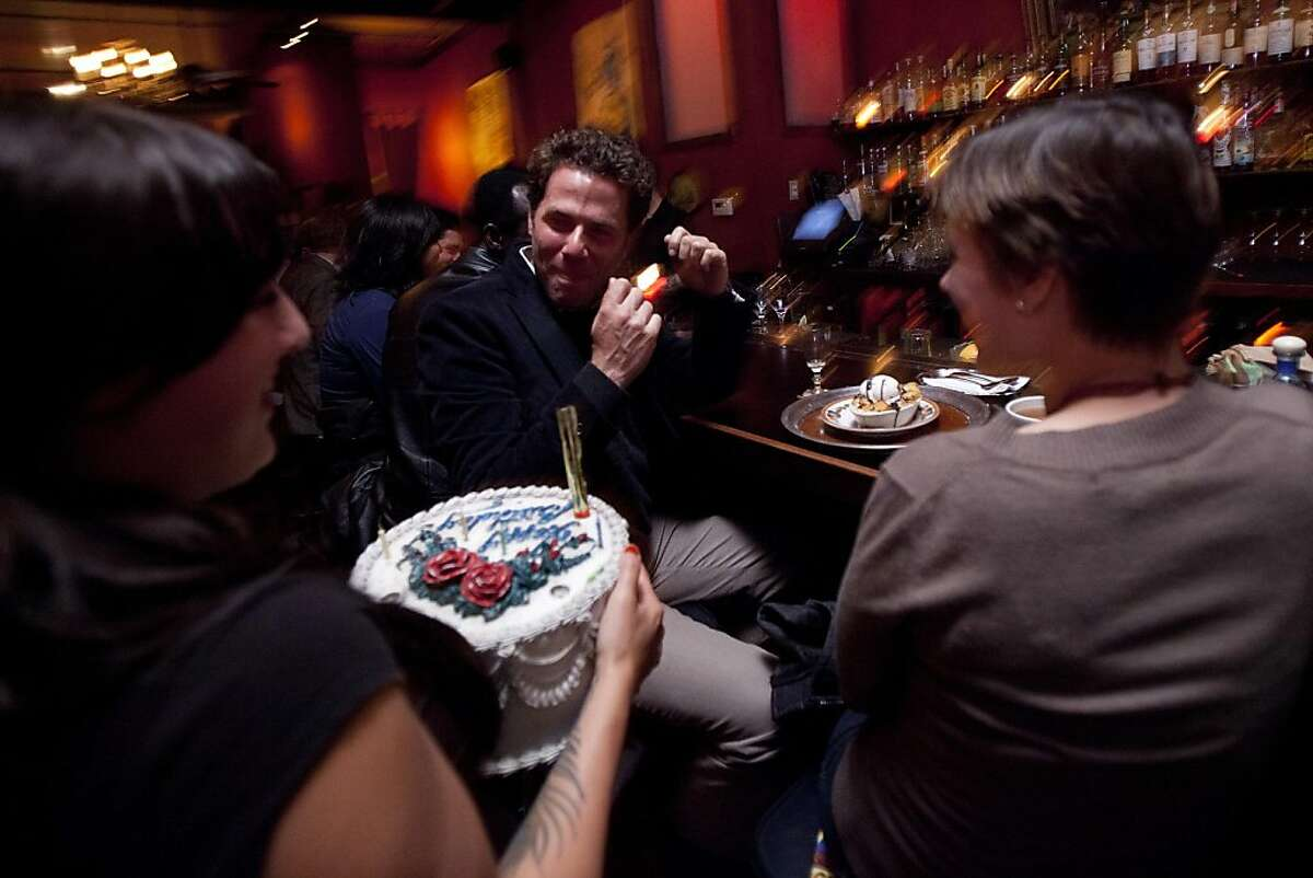 Greg Freemon, center, reacts after discovering a Chocolate Chip Bread Pudding with Chocolate Chip Ice Cream hidden beneath a birthday cake cover at Luna Park in San Francisco, Calif. on Thursday, May 26, 2011.