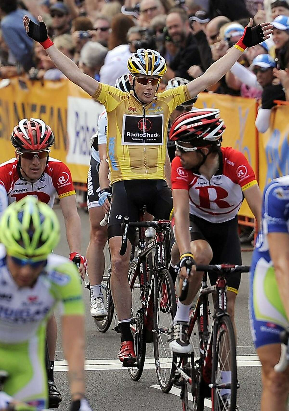 Chris Horner, center, celebrates as he crosses the finish line of the final stage of the Tour of California cycling race as teammates Levi Leipheimer, left, and Haimar Agirre Zubeldia, of Spain, ride nearby on Sunday, May 22, 2011, in Thousand Oaks, Calif. Horner won the race.