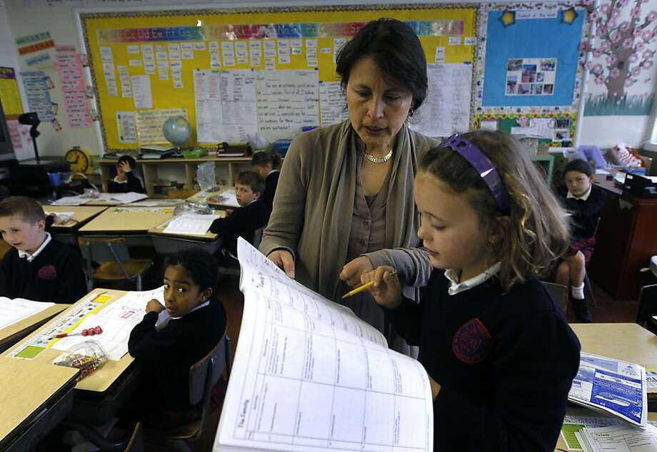Spanish teacher Claudia Portillo helps second grader Sally McCarthy at the Saint Philip School in San Francisco, Calif. on Tuesday, May 17, 2011. With foreign language programs being cut at the high school level, more and more language classes are being offered in elementary schools. Photo: Paul Chinn, The Chronicle