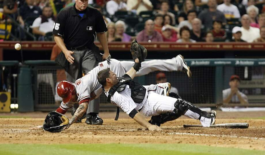 Arizona Diamondbacks third baseman Ryan Roberts (14) runs into Houston Astros catcher Humberto Quintero (55) at home plate as Roberts scored in the seventh inning injuring Quintero during their baseball game at Minute Maid Park, Friday, May 27, 2011, in Houston. Photo: Johnny Hanson, AP