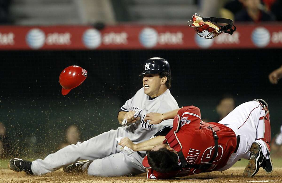 New York Yankees' Mark Teixeira scores over Los Angeles Angels catcher Bobby Wilson on a hit by Robinson Cano during the third inning of a baseball game in Anaheim, Calif., Friday, April 23, 2010. Wilson was carried off the field after the play. (AP Photo/Chris Carlson)