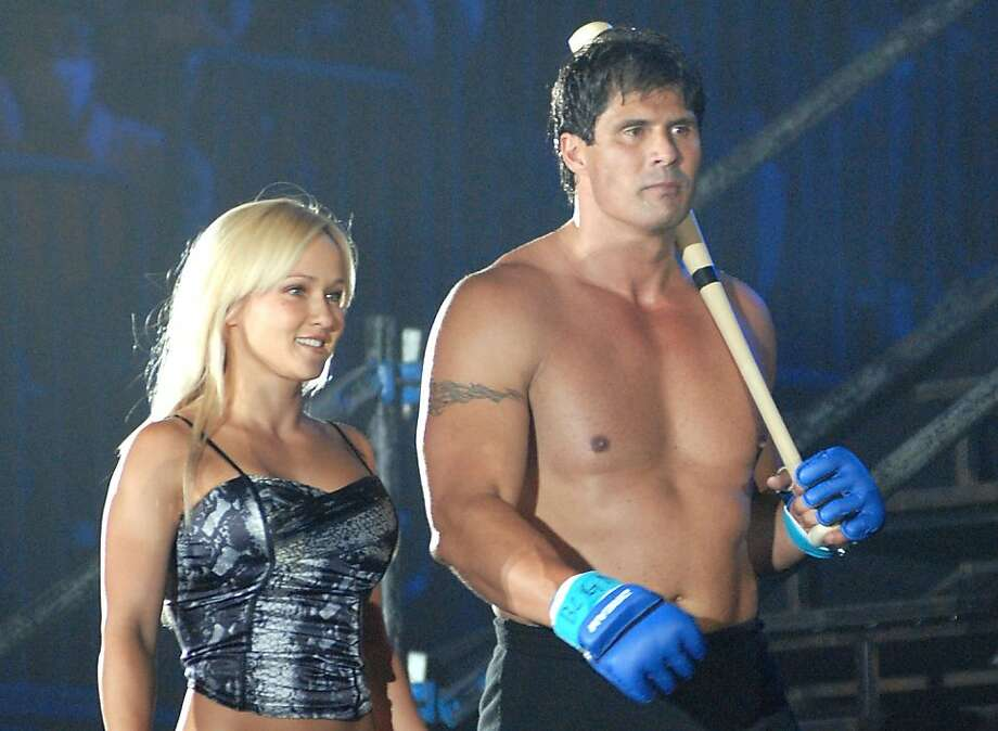 Former Oakland Athletics slugger Jose Canseco (R) and Heidi Northcott walk to the ring holding a bat prior to the match with Choi Hong-man at first Round of Super Hulk Tournament during Dream.9 at Yokohama Arena on May 26, 2009 in Yokohama, Kanagawa, Japan. Canseco lost at 1 minute 17 seconds in the first round. Photo: Hiroki Watanabe, Getty Images