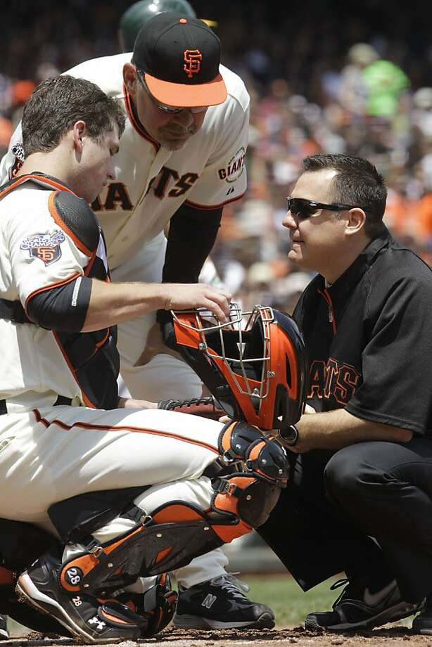 San Francisco Giants head trainer Dave Groeschner, right, and manager Bruce Bochy, center, check on the condition of catcher Buster Posey after Posey was hit by a pitch thrown by Oakland Athletics' Jonathan Sanchez in the second inning of an interleague baseball game, Sunday, May 22, 2011, in San Francisco. Photo: Ben Margot, AP
