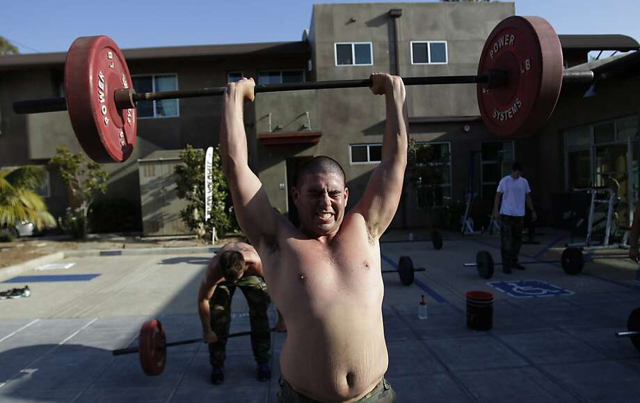 In this May 12, 2011 photo, men who wished not to be identified lift weights during a workout designed to mirror a US Navy SEAL's at the SEALFIT exercise center in Encinitas, Calif. Excitement over the Navy SEAL team's takedown of Osama bin Laden is fueling interest in fitness programs run by former members of the elite force. Photo: Gregory Bull, Associated Press