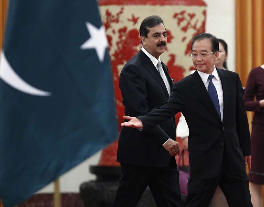 China's Premier Wen Jiabao, right, shows the way to Pakistan's Prime Minister Yousuf Raza Gilani, center, during a welcome ceremony at the Great Hall of the People in Beijing, on Wednesday May 18, 2011. Photo: Jason Lee, Associated Press