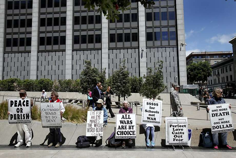 Protesters sit in front of the Federal building as the lunch crowd walks past Thursday May 26, 2011. About a dozen people, called the Non-Violent Vigil for Peace and Justice, gather near the San Francisco Federal building every week at the noon hour to protest the wars in Iraq and Afghanistan. Photo: Brant Ward, The Chronicle