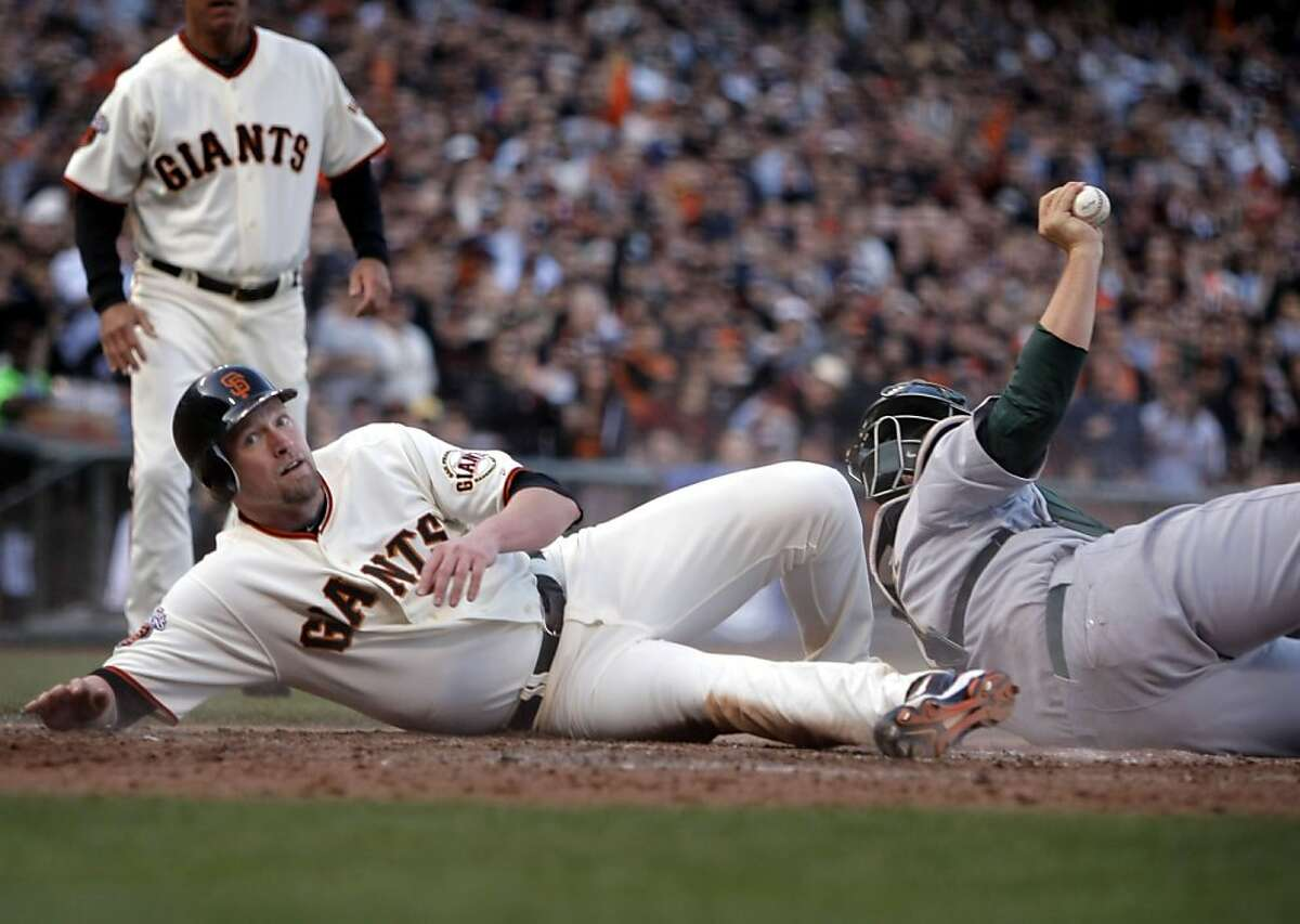 San Francisco Giants' Aubrey Huff gets tagged out at home by Oakland Athletics' Landon Powell during the 6th inning. As the San Francisco Giants take on the Oakland Athletics at AT&T Park in San Francisco, Calif., on Saturday, May 21, 2011.