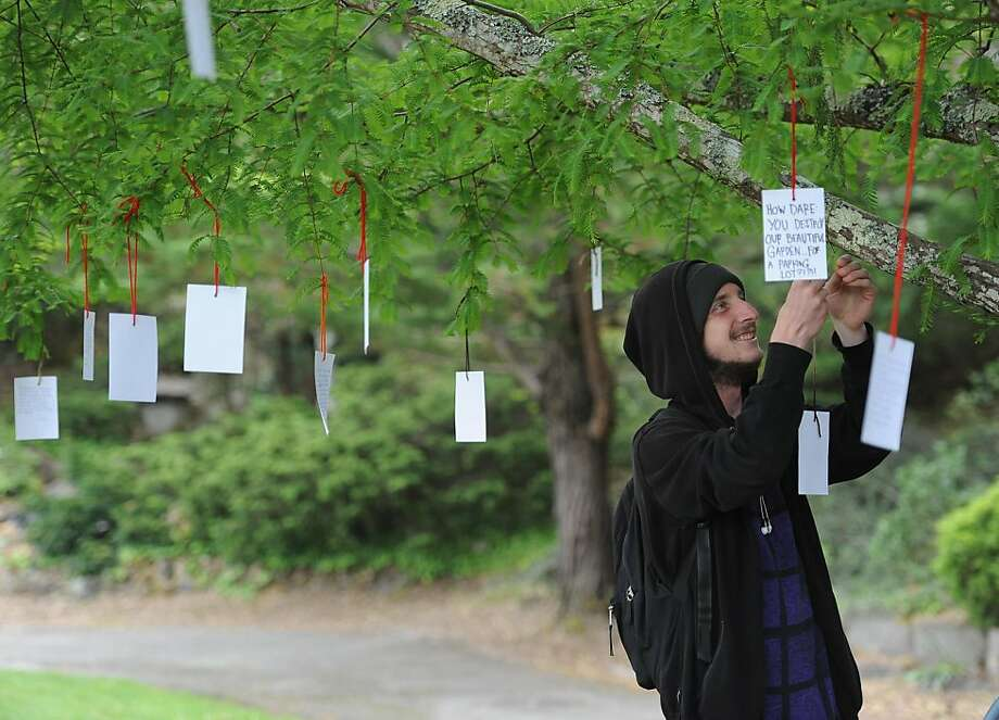 Sean Carhart hangs a personal note on a tree where students gathered at the Horticulture Department Gardens at the College of San Mateo campus in San Mateo, CA. on Wednesday, May 11, 2011. Against the wishes of students and faculty, the college plans to rip up hundreds of rare plants, including a Dawn Redwood, to put in a parking lot. Photo: Susana Bates, Special To The Chronicle