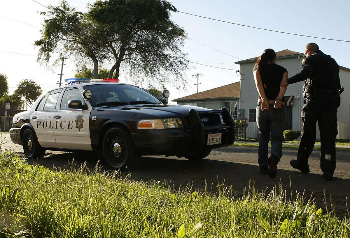 Officer Phillip Sanchez escorts a woman to his patrol car after placing her under arrest at the intersection of 8th Street and and Lucas Street in Richmond Calif, on Thursday, May 26, 2011.