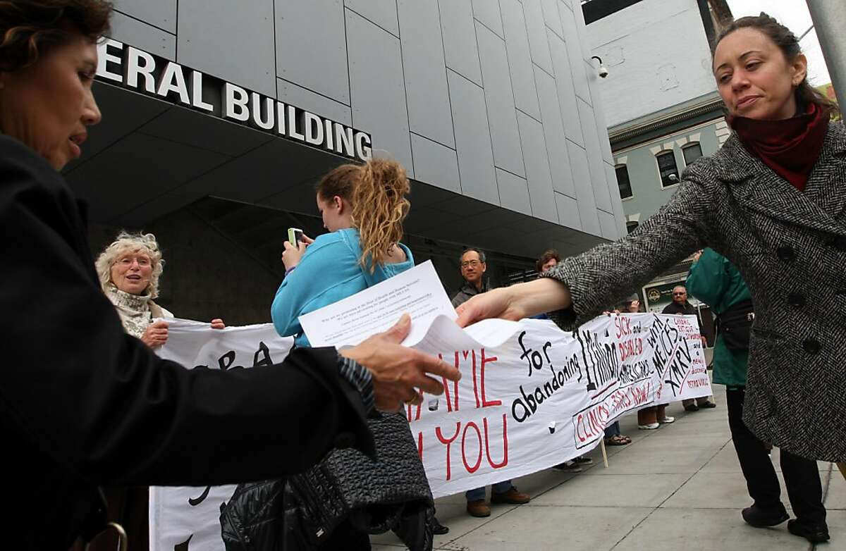 Medical worker, Melissa Ayres right, hands out flyers during a Bay Area chronic fatigue protest in front of the offices of the U.S. Department of Health and Human Services in San Francisco Wednesday May 25, 2011. The group is pleading for more research funding for the illness. Patients have frustratingly little information about what causes their condition and what they can do to treat it.