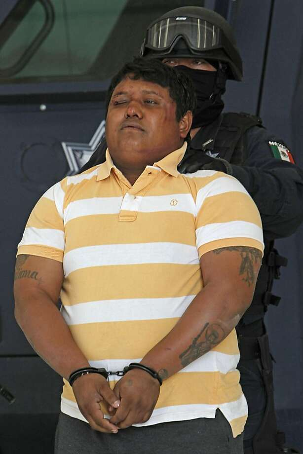 """A police officer escorts Julio de Jesus Radilla Hernandez, aka """"El Negro"""" as he is presented to the press at the federal police headquarters in Mexico City,Wednesday, May 25, 2011.  Mexico's federal police said Radilla Hernandez is allegedly responsible for ordering the March 27 murder of Juan Francisco Sicilia, son of Mexican poet Javier Sicilia and six other people. Photo: Marco Ugarte, AP"""
