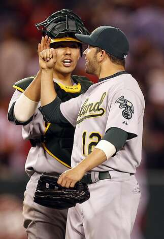 Oakland Athletics right fielder David DeJesus, right, and catcher Kurt Suzuki celebrate their win against the Los Angeles Angels during a baseball game in Anaheim, Calif., Tuesday, May 24, 2011. Photo: Chris Carlson, AP