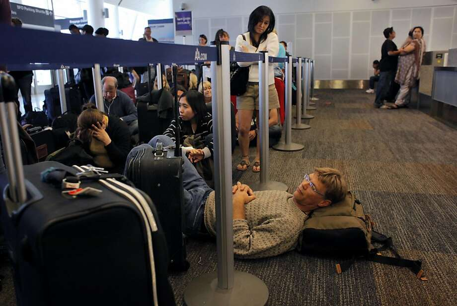 Chuck Crouse naps as he waits inline in Terminal 2  at the San Francisco International Airport, Wednesday May 25, 2011, in San Francisco, Calif. He was traveling to Washington D.C. for a work and to visit his sister.  Due to the extreme weather conditions in the midwest and the upcoming Memorial Day Holiday lines are long for the travelers. Photo: Lacy Atkins, The Chronicle