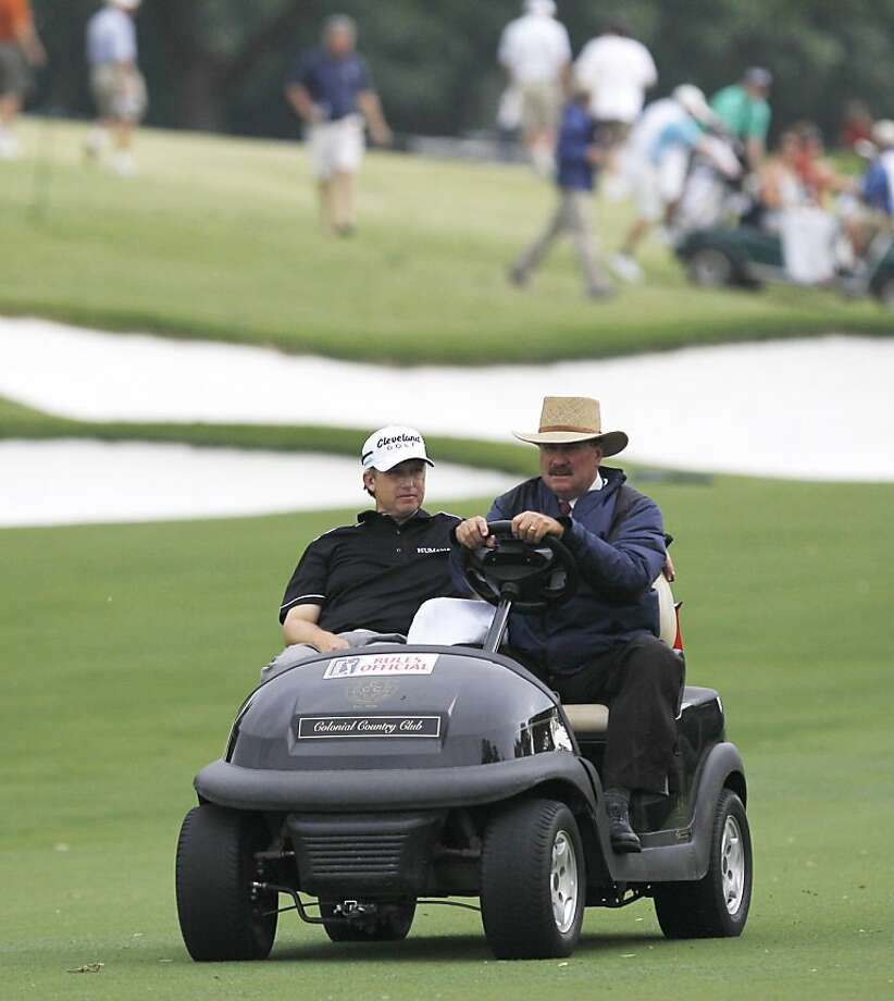 David Toms, left, is driven off the golf course by PGA official Slugger White after play was suspended due to weather during the second round of play at the Colonial golf tournament in Fort Worth, Texas, Friday, May 20, 2011. Photo: LM Otero, AP