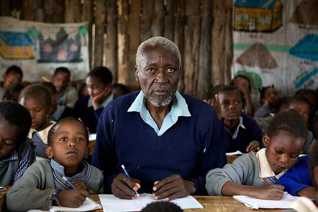 Maruge (Oliver Litondo) at his desk, towering over his classmates.  The First Grader Photo: Kerry Brown 2009, National Geographic Entertainmen