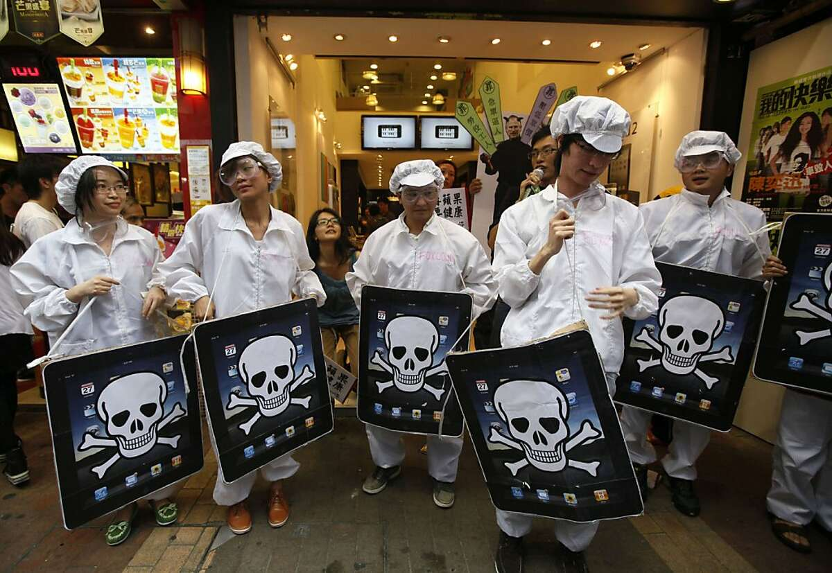 FILE - In this file photo taken Saturday, May 7, 2011, local and mainland Chinese university students, dressed as the Foxconn workers, hold mock iPads with a skeleton print outside an Apple Premium Reseller shop in Hong Kong. An explosion that occurred onMay 20, 2011, at one of two factories that make Apple's new iPad 2 highlights the risks of a global manufacturing strategy that has cut costs but concentrates production in a few locations.