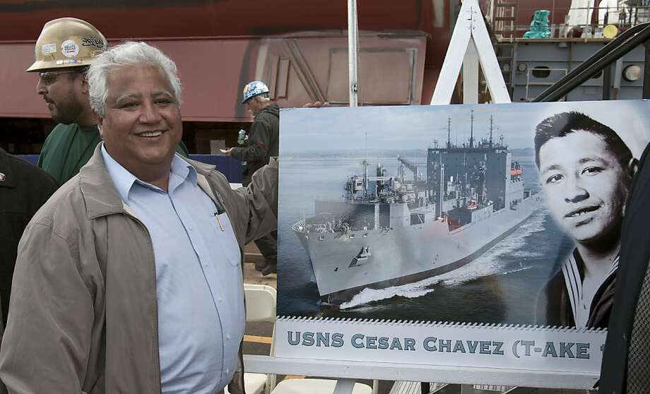 Paul Chavez, the son of former labor leader Cesar Chavez poses for a picture alongside an image of his father during his stint in the Navy during a naming ceremony for a new Navy ship at a shipyard Wednesday, May 18, 2011, in San Diego. Navy Secretary RayMabus made the formal announcement Wednesday that the Navy has named the last of 14 new cargo ships after the late farm labor leader. Photo: Gregory Bull, AP