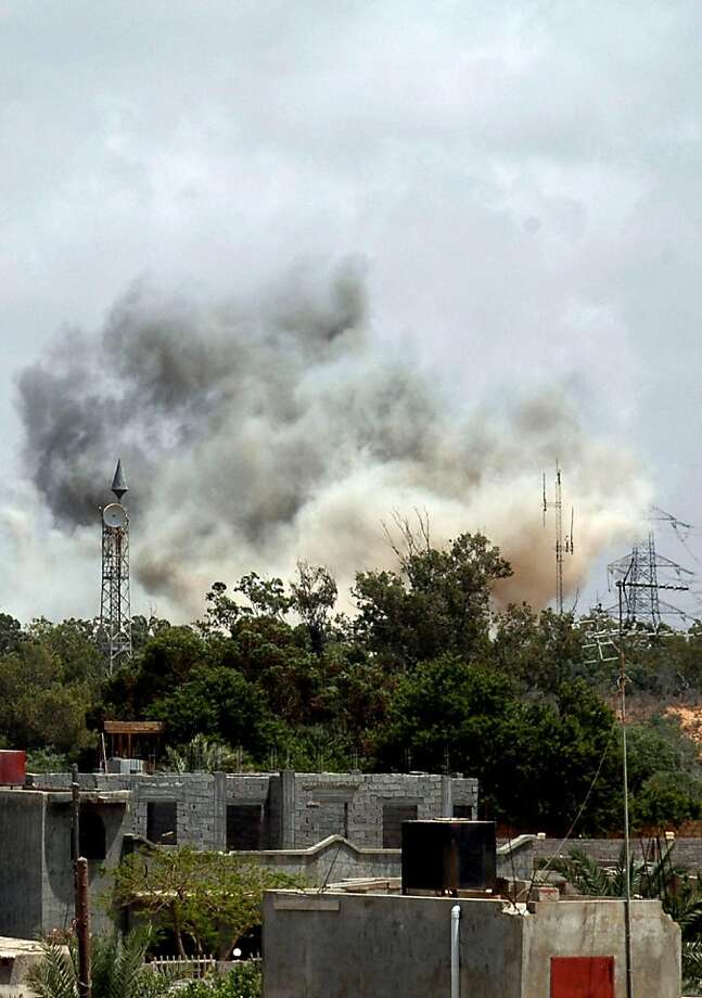Smoke billows behind the trees following an air raid on the area of Tajura, 30 km east of Tripoli, as loud explosions rocked the Libyan capital on May 24, 2011 when NATO unleashed its heaviest blitz yet of the area in a bid to speed up the ouster of Libyan leader Moamer Kadhafi. Photo: -, AFP/Getty Images