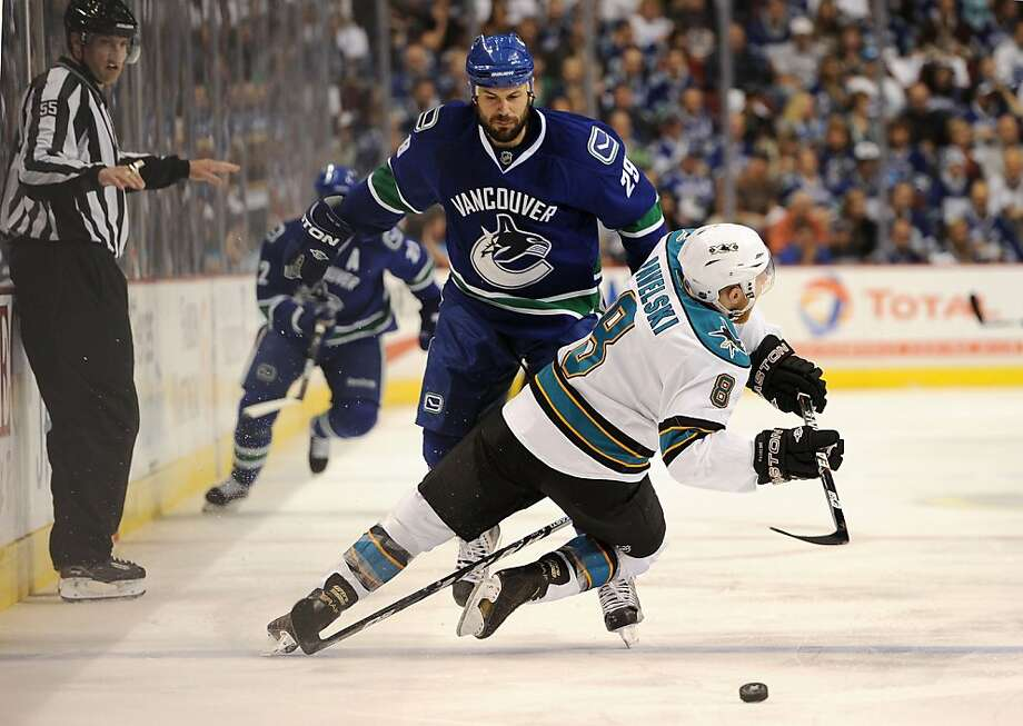 VANCOUVER, CANADA - MAY 18:  Aaron Rome #29 of the Vancouver Canucks trips up Joe Pavelski #8 of the San Jose Sharks at the blue line in the first period in Game Two of the Western Conference Finals during the 2011 Stanley Cup Playoffs at Rogers Arena onMay 18, 2011 in Vancouver, British Columbia, Canada. Rome was called for a penalty. Photo: Harry How, Getty Images