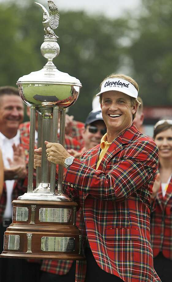 David Toms wears the winner's jacket and holds up the Colonial trophy after winning the golf tournament in Fort Worth, Texas, Sunday, May 22, 2011. Photo: LM Otero, AP