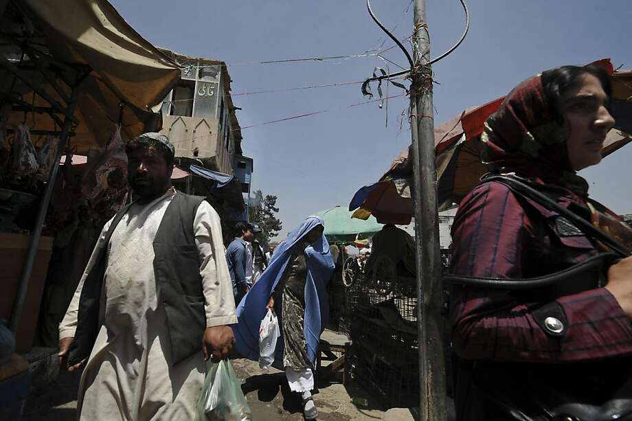 "Afghans make their way through a bazaar in Kabul on May 23, 2011. An Afghan Taliban spokesman said it was ""not possible at all"" that their leader Mullah Omar was dead, after an Afghan intelligence source said he had been killed in Pakistan. Photo: Shah Marai, AFP/Getty Images"