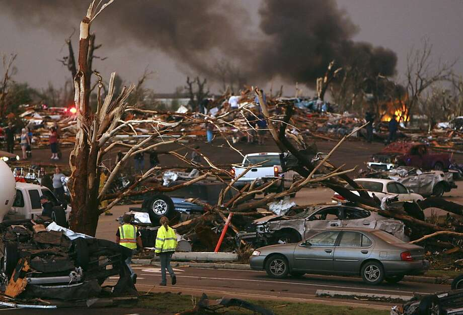 Emergency personnel walk through a neighborhood severely damaged by a tornado near the Joplin Regional Medical Center in Joplin, Mo., Sunday, May 22, 2011. A large tornado moved through much of the city, damaging a hospital and hundreds of homes and businesses. Photo: Mark Schiefelbein, AP