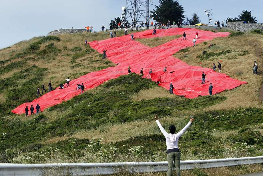 Anadeise Villasenor Munoz waves her arms to fellow volunteers after finishing the red ribbon. AIDS activists and volunteers team up to stake down red tarps to create a giant red ribbon on the side of Twin Peaks in San Francisco, Calif., on Sunday, May 22, 2011. Photo: Thomas Levinson, The Chronicle