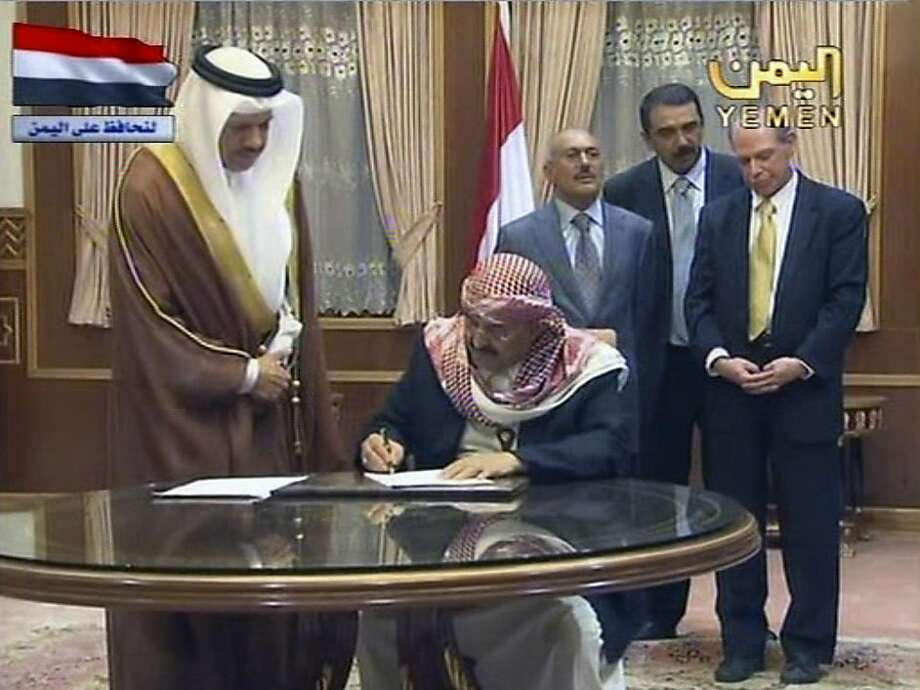 In this image taken from Yemen State TV, Sunday May 22, 2011, showing Yemen President Ali Abdullah Saleh, behind 3rd from right, and U.S. ambassador, yellow tie at right, witnesses unidentified ruling party leaders signing an agreement for the president to step down in 30 days, during a ceremony at the Presidential Palace in Sanaa, Yemen.  President Ali Abdullah Saleh did not sign the documents, and State TV said that Saleh will not sign the deal unless opposition leaders are present. Others unidentified. (AP Photo/Yemen State TV) TV OUT Photo: AP