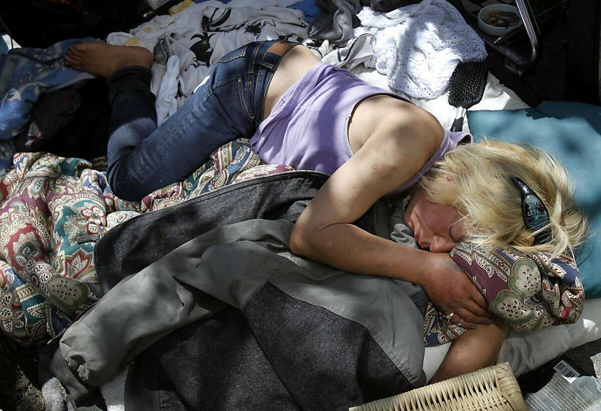 Vina, a homeless person, catches a nap before panhandling near Mission and Market Streets Thursday May 12, 2011. Vina has been homeless for years on the streets of San Francisco. The San Francisco, Calif., homeless count for 2011 reveals a slight decline in city homeless, but a rise in families who need assistance.