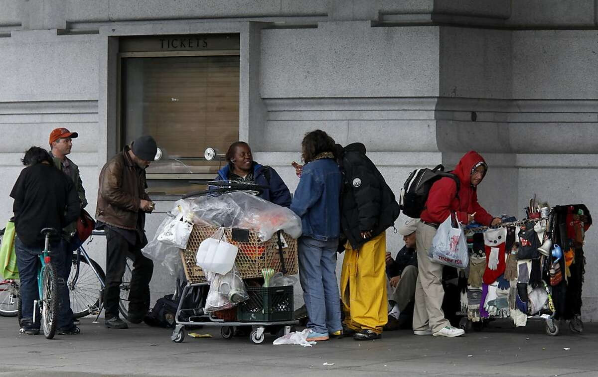 A group of homeless people stayed dry Monday May 16, 2011 under the overhang at the Bill Graham Civic Auditorium in San Francisco, Calif.