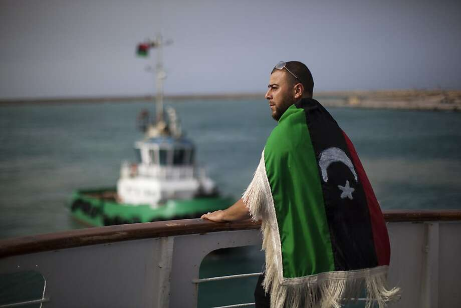 A man wearing a pre Moammar Gadhafi flag observes the port while arriving aboard a boat rented by International Organization for Migration (IOM) carrying food, Non-Governmental Organizations (NGO) workers and journalists at port in Misrata, Libya, Saturday, May 21, 2011. Photo: Rodrigo Abd, AP