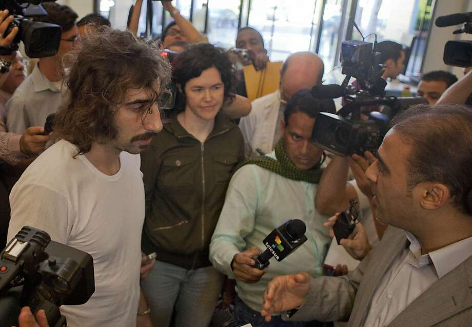 Freed American freelance journalist Clare Morgana Gillis, center left and Spanish photographer Manu Brabo, far left talk with Libyan government spokesman Moussa Ibrahim upon their arrival to a hotel where most of international media stays in Tripoli, Libya, Wednesday, May 18, 2011. Four journalists held for allegedly illegally entering the country were freed by Libyan authorities. (AP Photo/Darko Bandic) Photo: Darko Bandic, AP