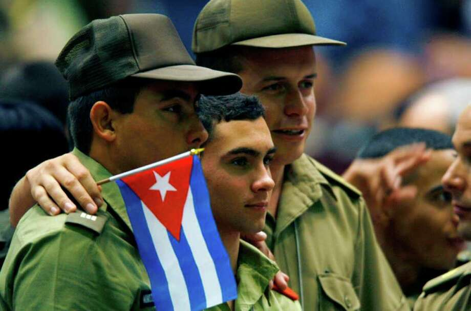 Elian Gonzalez, center, posses for a photograph along with two Cuban army soldiers during the UJC, Union of Young Communists, congress in Havana Sunday April 4, 2010. Photo: Ismael Francisco, AP / Prensa Latina
