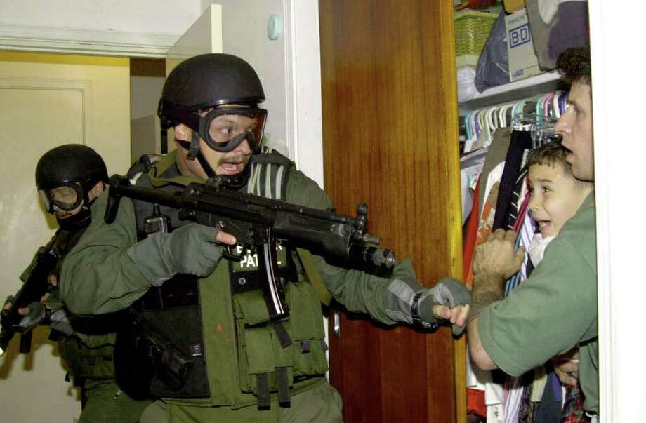 Donato Dalrymple, far right, holds 6-year-old Elian Gonzalez inside the bedroom of Lazaro Gonzalez during the pre-dawn hours Saturday, April 22, 2000, as government agents stormed the Miami home to seize custody of the boy. Photo: ALAN DIAZ, AP / AP