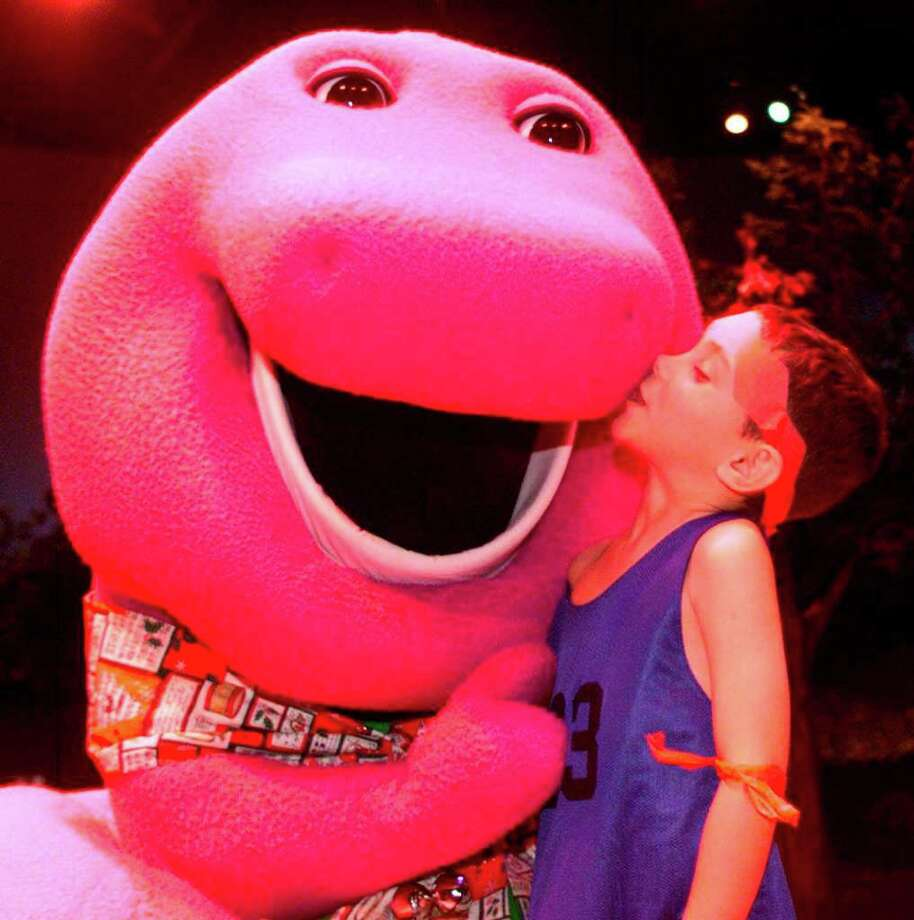 Six-year-old Elian Gonzalez gives Barney the dinosaur a kiss while visiting Universal Studios Florida in Orlando on Monday, Dec. 13, 1999. Photo: RICK FOWLER, AP / UNIVERSAL STUDIOS