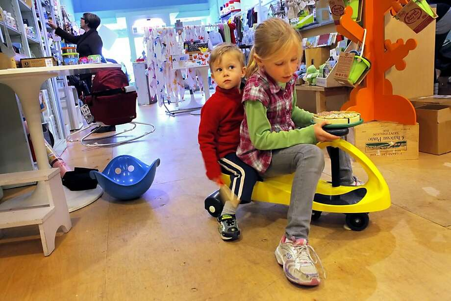 Olivia Brune  and her brother Sebastian play with a pizza puzzle and a plasma car in the children shop the Monkey Bars,Tuesday Monday May 17, 2011, in Alameda, Calif. Mary is extra cautious about the products she buys since eighty percent of baby products contain chemical flame retardants that are either untested or known to be toxic. Photo: Lacy Atkins, The Chronicle