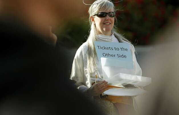 A woman passes out tickets to the other side as she joins a large group outside the headquarters of Family Radio in Oakland on Saturday. Photo: Michael Macor, The Chronicle