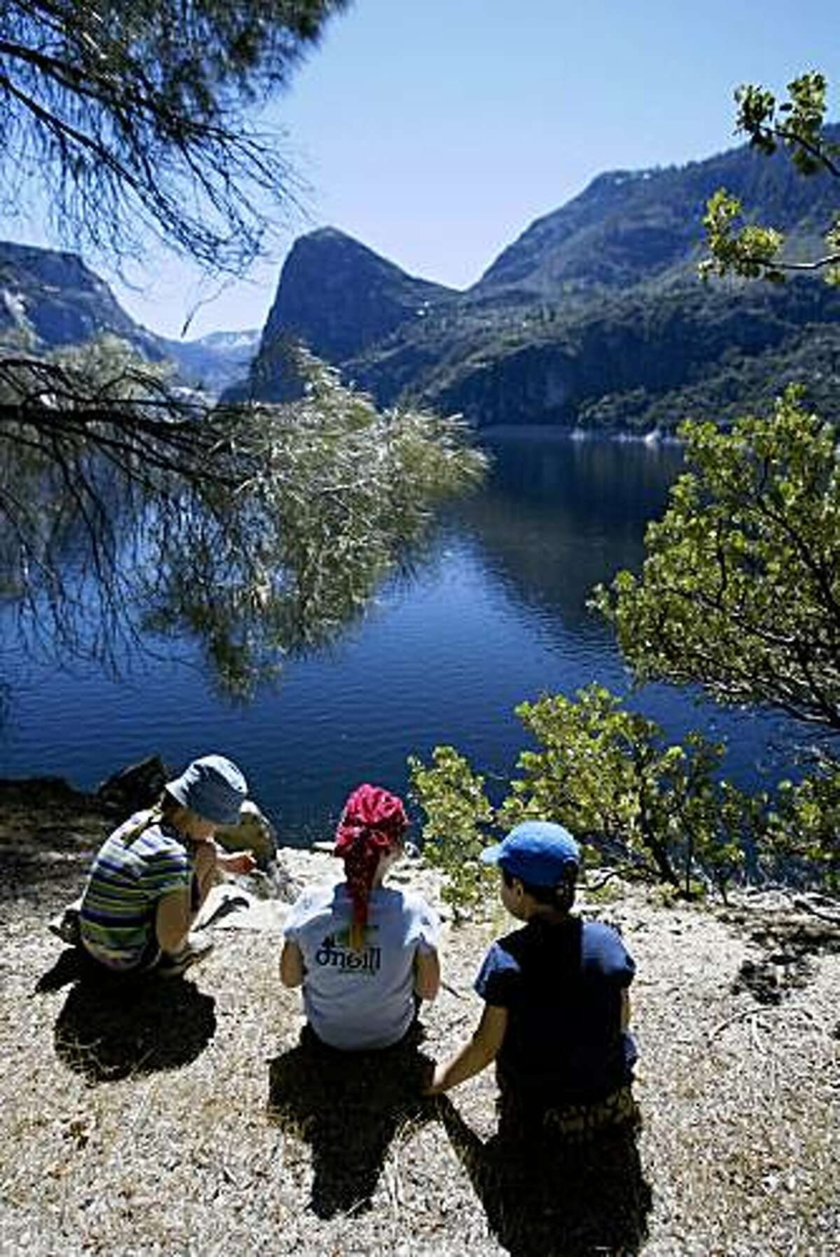 Left to right, Quincy Stivers, 7, Maddie Marchand, 7, and Aiden Stivers, 5, take a break from hiking while on a tour of the Hetch Hetchy area with their parents and a group folks interested in Restoring Hetch Hetchy.