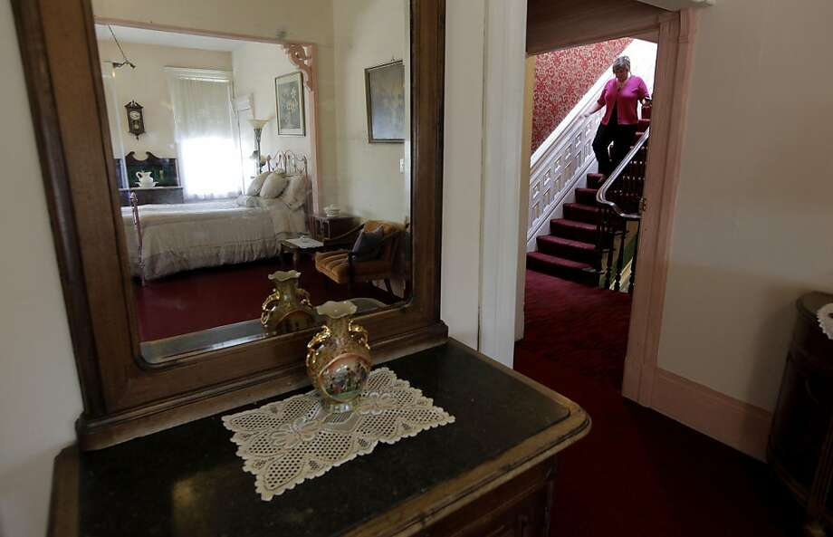 Realtor, Karrie Camerzon walks the stairs near one of the many rooms at the Burlington Hotel in Port Costa, Ca., on Thursday May 12, 2011. The hotel which was originally built in 1883 is currently up for sale. Photo: Michael Macor, The Chronicle